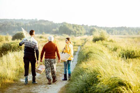Junger Mann und Frau, die auf dem Picknick mit dem älteren Großvater in Pullovern spazieren gehen und eine gute Zeit zusammen in der Natur verbringen