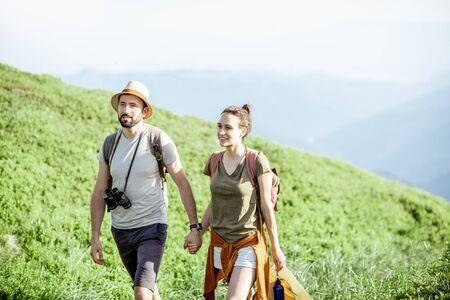 Hermosa pareja caminando con mochilas en el valle verde, mientras viaja en lo alto de las montañas durante el verano Foto de archivo