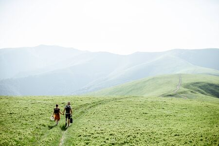 Couple walking with backpacks on the green meadow, traveling in the mountains during the summer time, wide landscape view