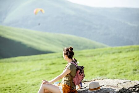 Woman enjoying landscape view on the mountains with paraglider flying on the background Zdjęcie Seryjne