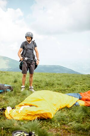Well-equipped man preparing for the paraglider flight, standing on the green meadow high in the mountains