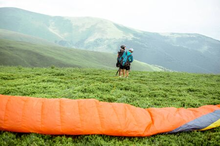 Well-equipped men preparing for the paraglider flight, walking to the the start position in the mountains