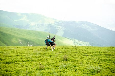 Men starting a paraglider flight, running on the green meadow high in the mountains Zdjęcie Seryjne