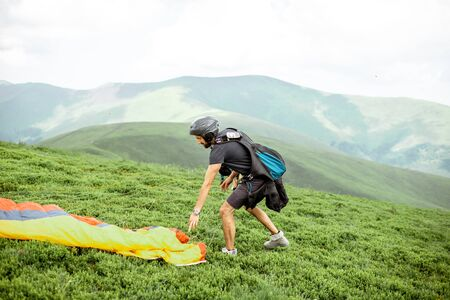 Well-equipped man preparing for the flight, laying out the paraglider on the green meadow high in the mountains