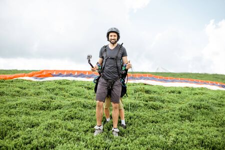 Portrait of a well-equipped man standing before the flight with paraglider in the mountains