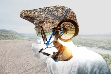 Double exposure of a man in protective helmet and professional cyclist riding on the mountains. Concept of a freeride and off road cycling