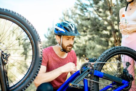 Young man in sportswear repairing bicycle on the forest road during the summer time