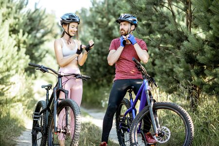 Man and woman cyclists wearing gloves and helmet, preparing for the bicycle riding while standing on the forest road during the summer time Imagens