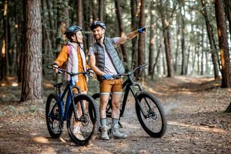 Young couple dressed casually standing together with mountain bicycles, traveling in the forest during the summer vacations