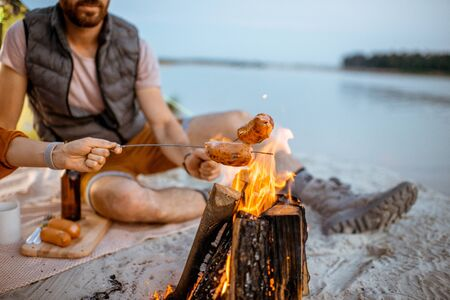 Young and cheerful couple cooking sausages at the fireplace, having a picnic at the campsite on the beach in the evening Stock Photo