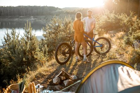 Young couple standing with mountain bicycles at the campsite, traveling in the forest near the lake on the sunset