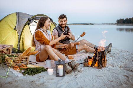 暖炉でソーセージを調理する若くて陽気なカップル、夕方にビーチのキャンプ場でピクニックをする