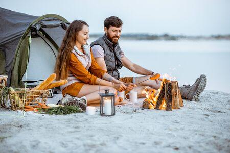 暖炉に座って若くて陽気なカップル、ソーセージを調理し、夕方にビーチのキャンプ場でピクニックをする