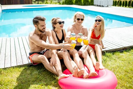 Group of happy friends sitting together by the swimming pool, talking and having fun drinking juice, enjoying the summer time