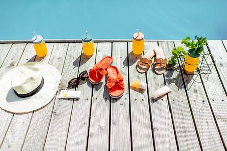 View on the poolside with accessories for summer vacations, drinks, slippers, sunglasses, sunscreen lotions and hat
