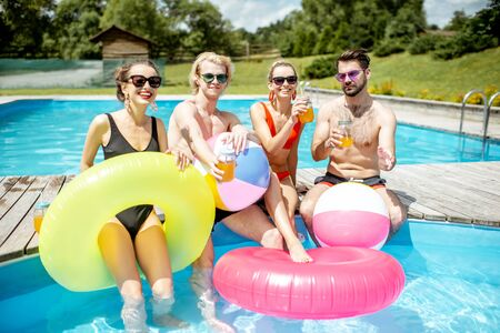 Group of a happy friends having fun, playing with inflatable balls and rings on the water pool outdoors during the summer time