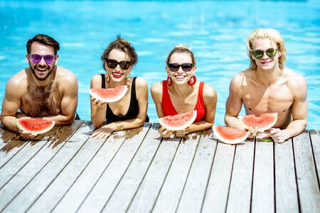 Group of a happy friends in swimwear eating watermelon while standing in the swimming pool outdooors during the summertime