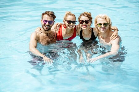 Portrait of a group of happy friends standing together in the swimming pool, having fun drinking juice and enjoying the summer time Foto de archivo