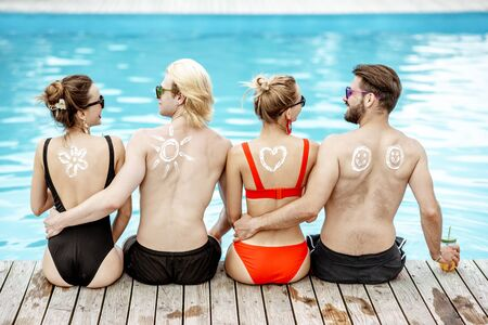 Friends with sun cream painted shapes on the shoulders sitting together on the poolside. Concept of a skin protection from a sun, rear view