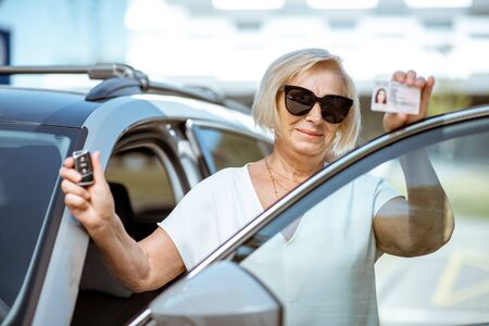 Portrait of a happy senior woman showing drivers license and keys, standing near the car outdoors. Concept of an active people during retirement age