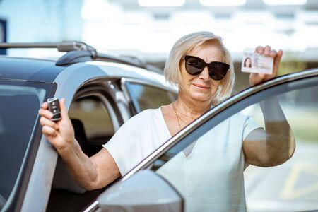 Ritratto di una donna anziana felice che mostra patente e chiavi, in piedi vicino all'auto all'aperto. Concetto di un popolo attivo durante l'età pensionabile