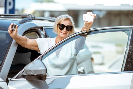 Portrait of a happy senior woman showing drivers license and keys, standing near the car outdoors. Concept of an active people during retirement age Stockfoto - 126766029