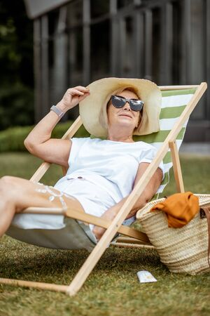 Beautiful senior woman in white clothes lying on the sunbed, relaxing in the park. Concept of rest and carefree life on retirement