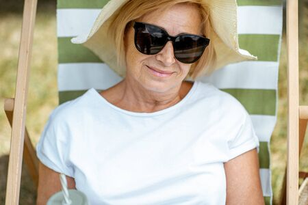 Portrait of a beautiful senior woman lying on the sunbed, relaxing in the park. Concept of rest and carefree life on retirement