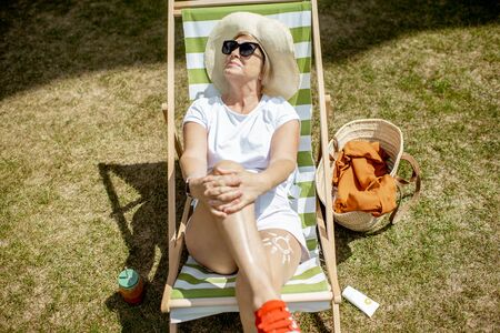 Beautiful senior woman in white clothes lying on the sunbed, view from above. Concept of rest and carefree life on retirement 版權商用圖片