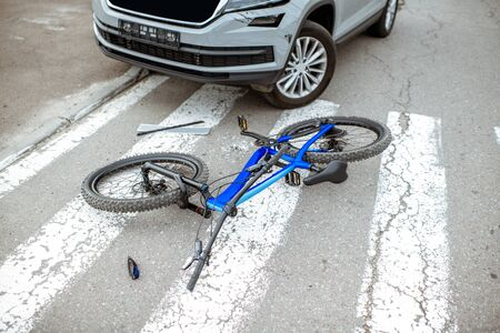 Scene of a road accident with car and broken bicycle lying on the pedestrian crossing