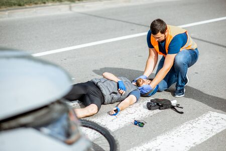 Road accident with injured cyclist on the pedestrian crossing with passerby pedestrian providing first aid fixing mens head Stok Fotoğraf