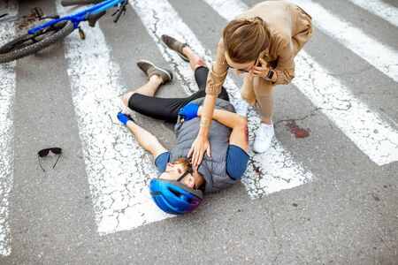 Road accident with injured cyclist lying on the pedestrian crossing near the broken bicycle, worried woman driver calling and checking mens pulse