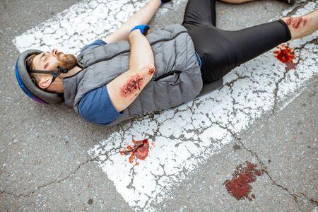 Cycliste blessé avec des blessures profondes allongé sur le passage pour piétons après l'accident de la route