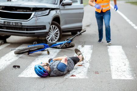 Road accident with injured cyclist lying on the pedestrian crossing near the broken bicycle and car driver running on the background