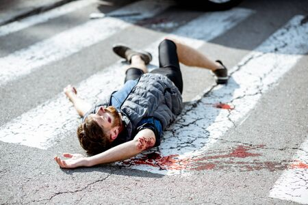Injured bleeding man lying on the pedestrian crossing after the road accident Stock Photo