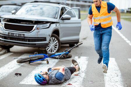 Accident de la route avec un cycliste blessé allongé sur le passage pour piétons près du vélo cassé et un conducteur de voiture courant sur l'arrière-plan Banque d'images