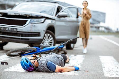 Accident de la route avec un cycliste blessé allongé sur le passage pour piétons près du vélo cassé et une conductrice et une voiture inquiètes en arrière-plan