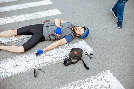 Homme blessé avec des blessures profondes allongé sur le passage pour piétons après l'accident de la route