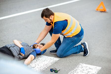 Road accident with injured cyclist on the pedestrian crossing with passerby pedestrian providing first aid fixing mens head Stock Photo