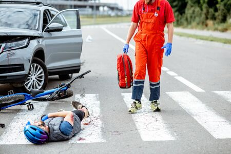 Road accident with injured cyclist lying on the pedestrian crossing, medic going to apply first aid Stock Photo