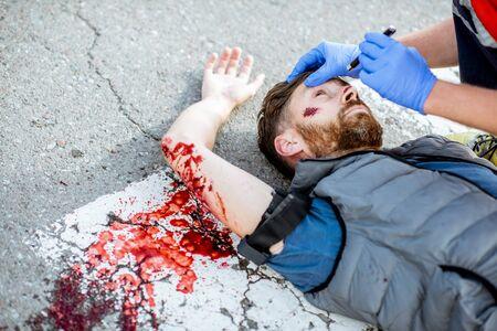 Medic vérifiant une personne inconsciente avec une lampe de poche, appliquant les premiers soins à la personne qui saigne sur la route après l'accident sur le passage pour piétons Banque d'images