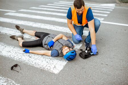 Road accident with injured cyclist on the pedestrian crossing with passerby pedestrian providing first aid