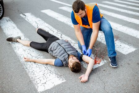 Man applying first aid to the injured bleeding person, wearing tourniquet on the arm after the road accident on the pedestrian crossing