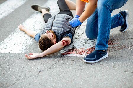 Homme appliquant les premiers soins à la personne blessée qui saigne, portant un garrot sur le bras après l'accident de la route sur le passage pour piétons
