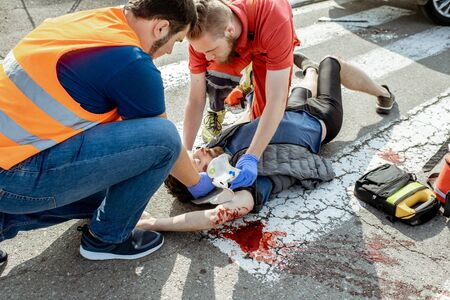 Ambluence workers applying emergency care to the injured bleeding man lying on the pedestrian crossing after the road accident Фото со стока - 127236081