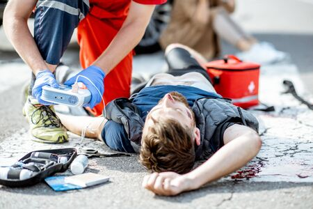 Ambluence worker applying emergency care with defibrillator to the injured bleeding man lying on the pedestrian crossing