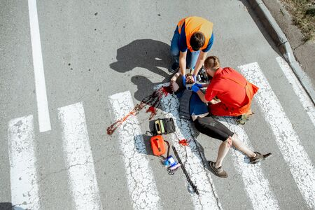Ambulance worker with man in road vest applying emergency medical care to the injured bleeding person lying on the pedestrian crossing after the accident, view from the above Stock Photo