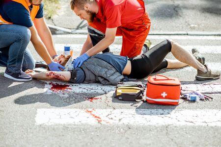Ambluence-Mitarbeiter, die den verletzten blutenden Mann, der nach dem Verkehrsunfall auf dem Fußgängerüberweg liegt, Notfallversorgung anwenden Standard-Bild