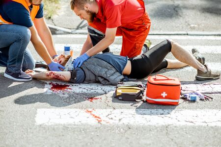 Ambluence workers applying emergency care to the injured bleeding man lying on the pedestrian crossing after the road accident