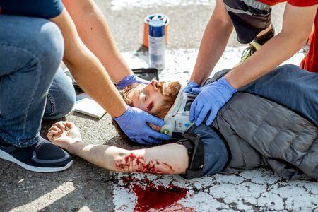 Les ambulanciers appliquent des soins d'urgence à l'homme blessé qui saigne, allongé sur le passage pour piétons après l'accident de la route